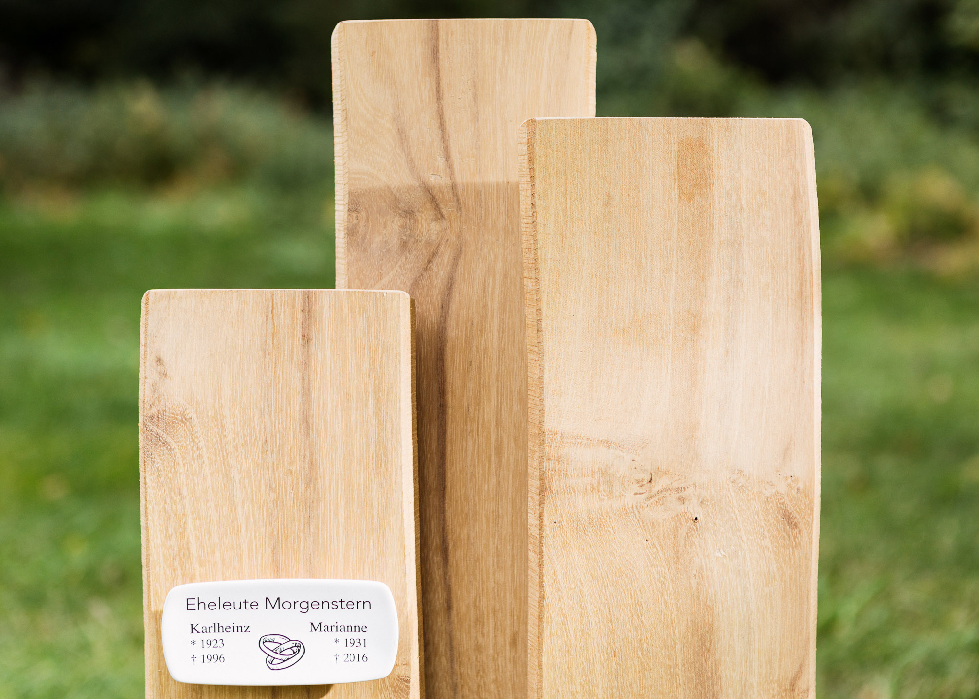 Grabmal aus geschichteten Naturholz-Lamellen mit vorgesetztem Emaille-Grabschild