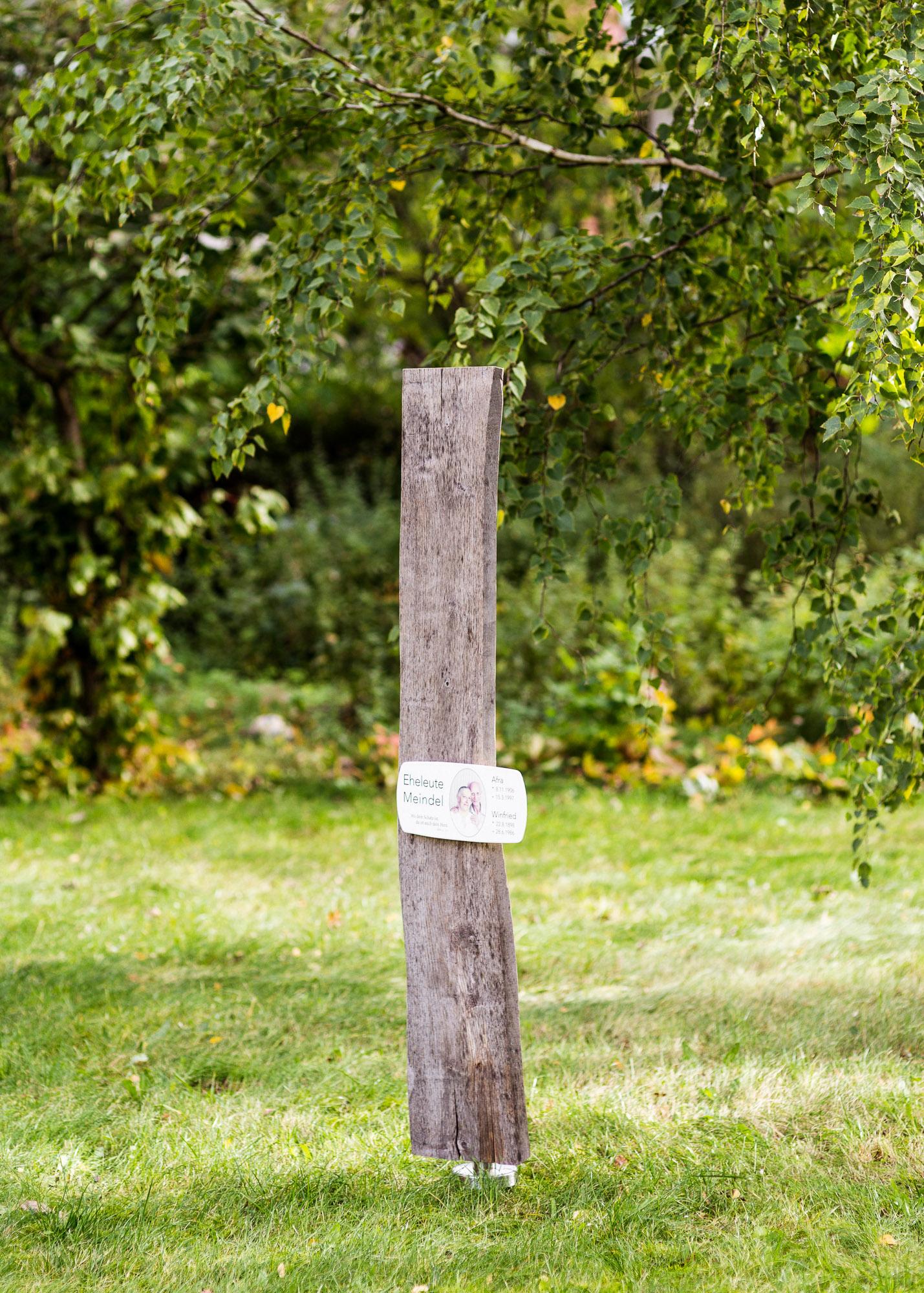 Familiengrabmal oder Ehegrab aus Naturholz vergraut und Emailleschild mit Foto